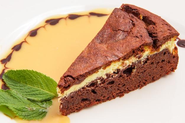 白で隔離されるクリームとチョコレートケーキ