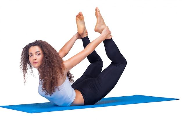 ヨガの練習をしている若いフィット女性のスタジオ撮影。
