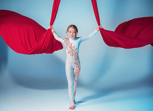 Изящная гимнастка выполняет воздушные упражнения