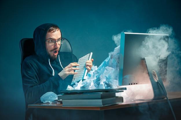 若者がノートパソコンの画面で叫び、スパムに怒っている現代のオフィスの机で働いているハンサムなビジネスマンを強調