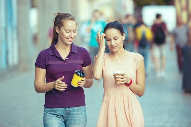 Красивые девушки, держа бумажную чашку кофе и наслаждаясь прогулкой в городе