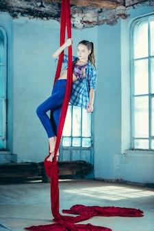Изящная гимнастка выполняет воздушные упражнения на чердаке