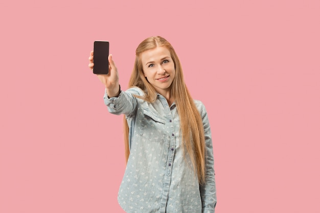 ピンクの壁に分離された空白の画面携帯電話を示す自信を持ってカジュアルな女の子の肖像画