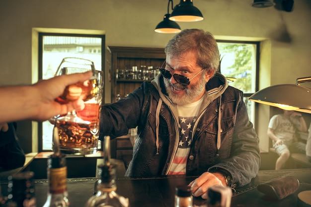 パブでビールを飲むシニアのひげを生やした男性