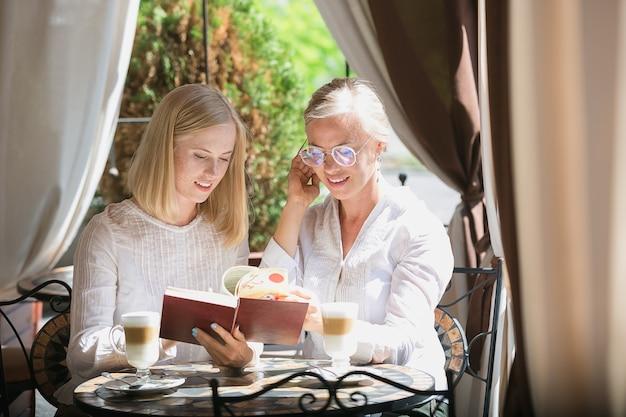 Портрет красивой зрелой матери и ее дочери, держа чашку, сидя у себя дома
