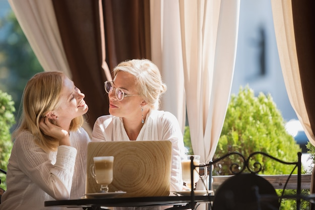 美しい成熟した母親と家に座ってカップを保持している彼女の娘の肖像画