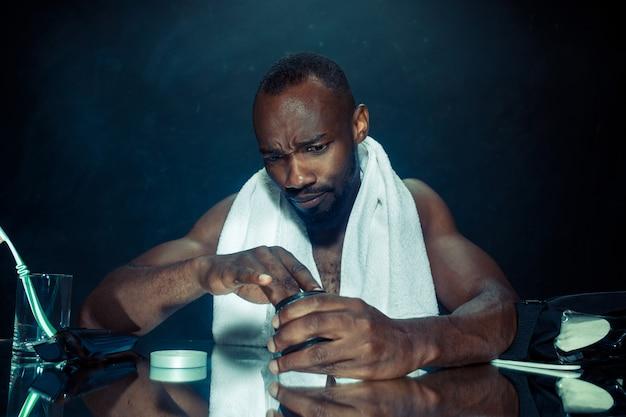 Молодой человек в спальне сидит перед зеркалом после того, как почесал бороду
