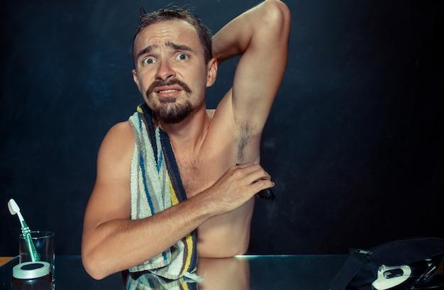 彼の脇の下を剃るハンサムな男の写真
