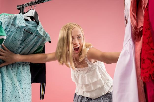 Молодая симпатичная девушка смотрит на платья и примеряет их, выбирая в магазине