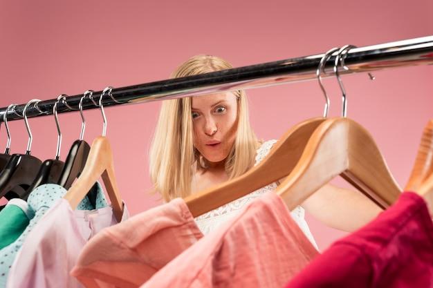 Молодая несчастная симпатичная девушка смотрит на платья и примеряет их, выбирая в магазине