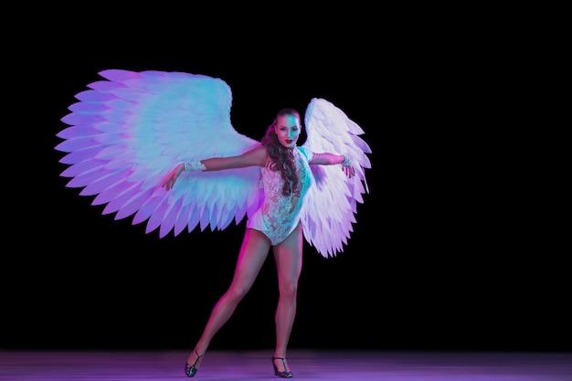 Молодая танцовщица с крыльями ангела в неоновом свете на черной стене