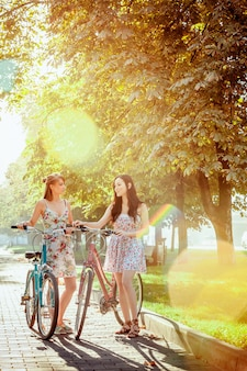 Две молодые девушки с велосипедами в парке