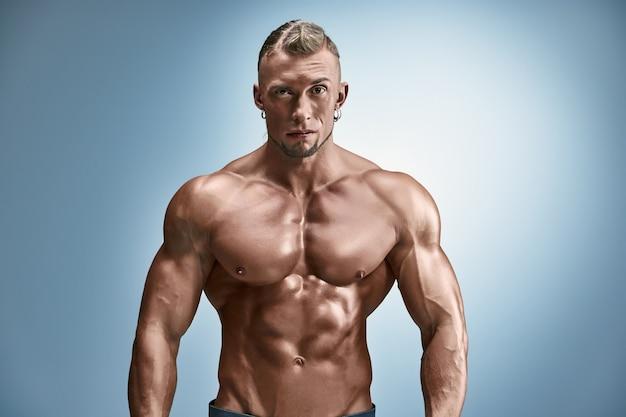 水色の壁に魅力的な男性の体ビルダー