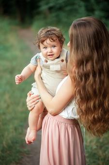 緑の芝生に対して彼女の小さな幼児の息子を抱いて若い美しい母親。夏の晴れた日に彼女の男の子との幸せな女。牧草地の上を歩く家族。