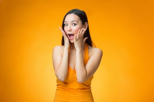 Удивленная китайская девушка на желтой стене