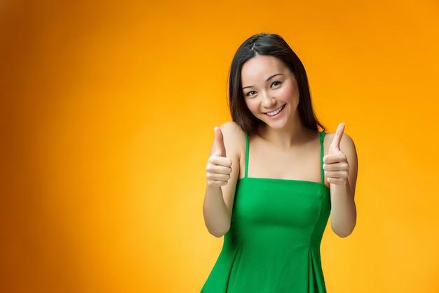 黄色の壁に幸せな中国の女の子
