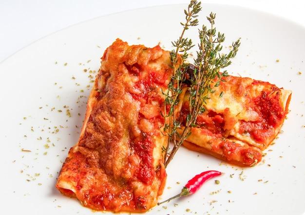 スパイシーなトマトソースとチーズのメキシコ風チキンエンチラーダ。