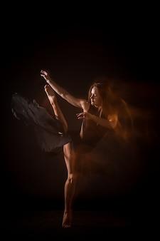 黒い壁の上で踊って若い美しいダンサー