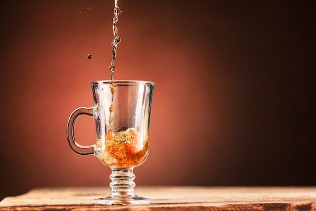 茶色は茶色の背景にお茶のカップから飲み物をはねかける