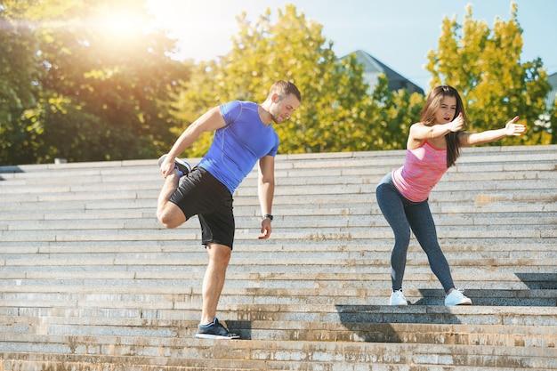 フィットのフィットネス女性と公園で屋外のストレッチ体操をしている男性