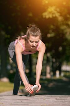 公園で屋外のストレッチ体操を行うフィットネス女性に適合