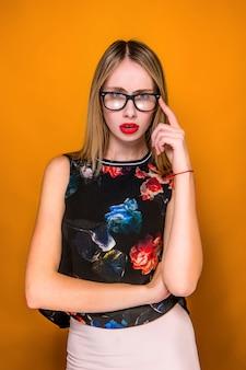 オレンジ色の壁に深刻な欲求不満の若い美しいビジネス女性