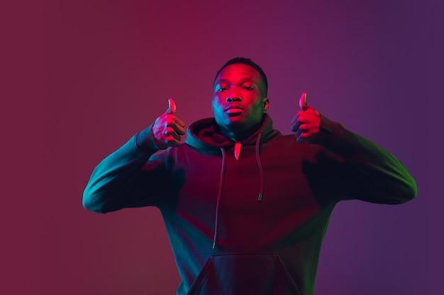 Портрет афро-американского человека, изолированные на градиентной стене в неоновом свете