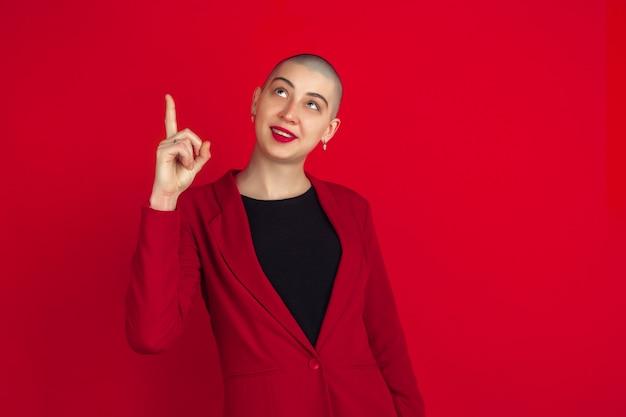 Портрет молодой женщины с причудливым появлением на красной стене