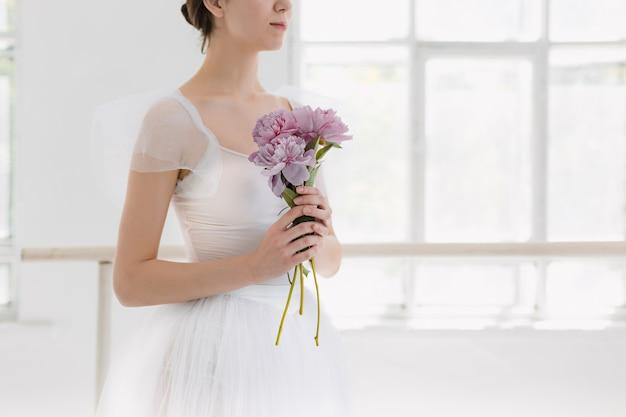 若い、信じられないほど美しいバレリーナが白いスタジオでポーズをとって踊っている