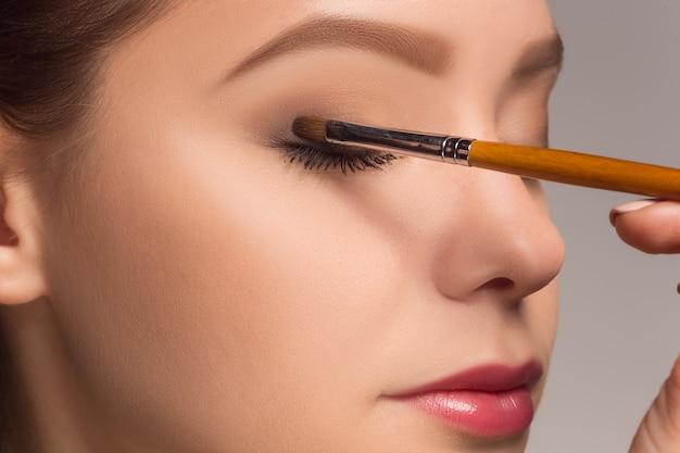 Красивые женские глаза с макияжем и кистью