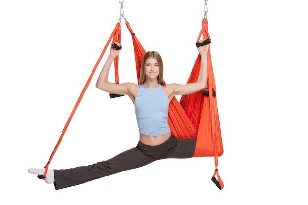 Молодая женщина делает антигравитационные упражнения йоги в растяжке шпагата