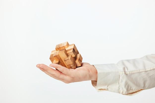 Мужские руки, держа деревянные головоломки.