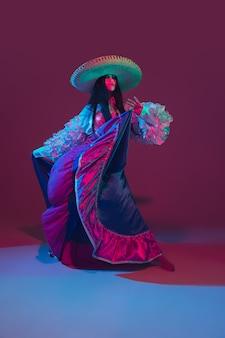 ネオンの光の中で紫色の素晴らしいシンコデマヨ女性ダンサー