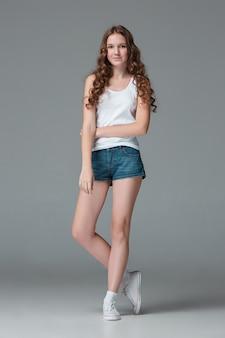 灰色の壁にデニムのショートパンツでスリムな若い女性の完全な長さ
