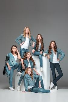 Модные девушки, стоящие вместе и над серым