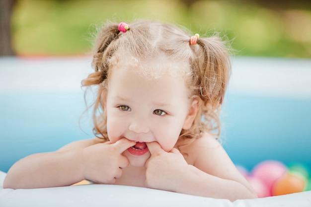 Маленькая девочка играет с игрушками в надувном бассейне в солнечный летний день