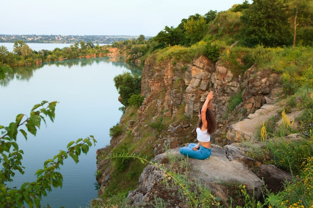 若い女性は川の近くのヨガを練習しています。