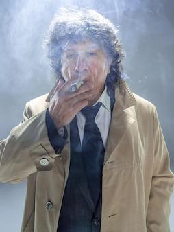 探偵またはマフィアのボスとして葉巻を持つシニア男性