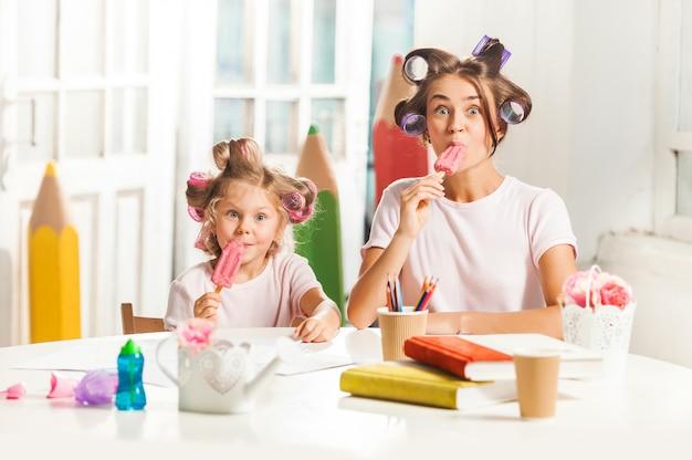 彼女の母親と一緒に座っているとアイスクリームを食べる少女