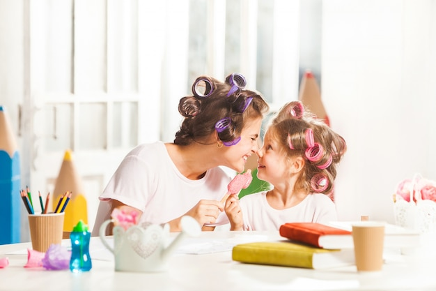 Маленькая девочка сидит со своей матерью и ест мороженое