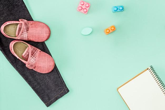 子供の靴とノート。学校のコンセプトに戻る。