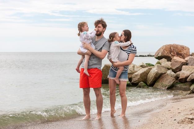 Семейный отдых родителей и детей на берегу моря летний день