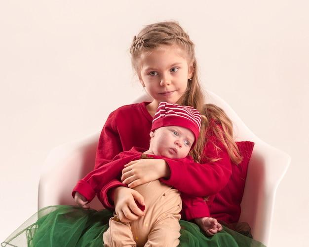 幸せな十代の少女は彼の生まれたばかりの赤ちゃんの妹を保持しています。家族愛。