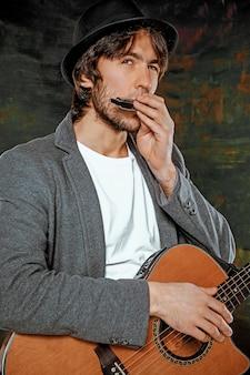 Крутой парень в шляпе играет на гитаре на сером
