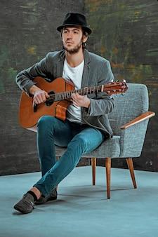 灰色でギターを弾く帽子のクールな男