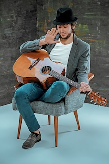 灰色のギターで座っているクールな男