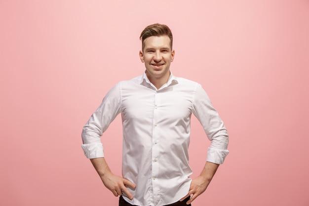 立っているとピンクの壁に笑みを浮かべて幸せなビジネスの男性。
