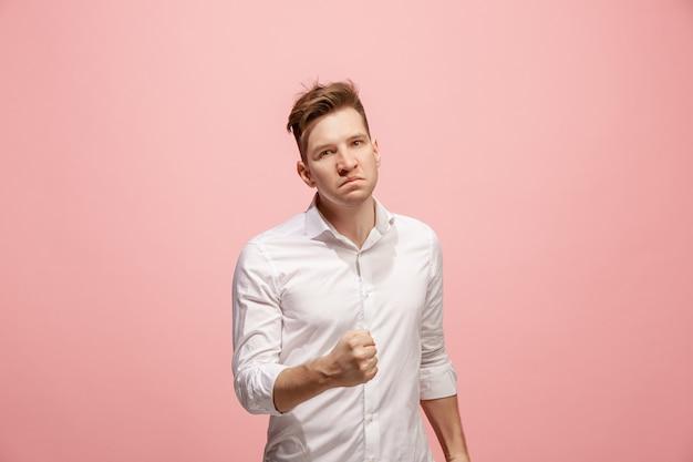 Молодой эмоциональный злой человек кричал на розовой стене