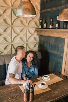 Счастливая молодая пара пьет кофе и улыбается, сидя в кафе
