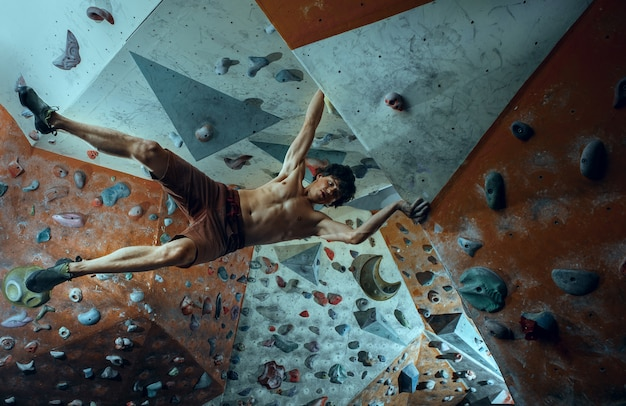 屋内で人工岩を登る無料の登山家の若い男